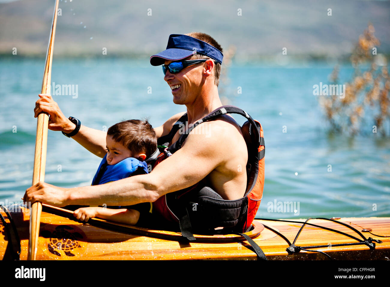 A Man Paddles Wooden Kayak With 3 Year Old Boy In His Lap
