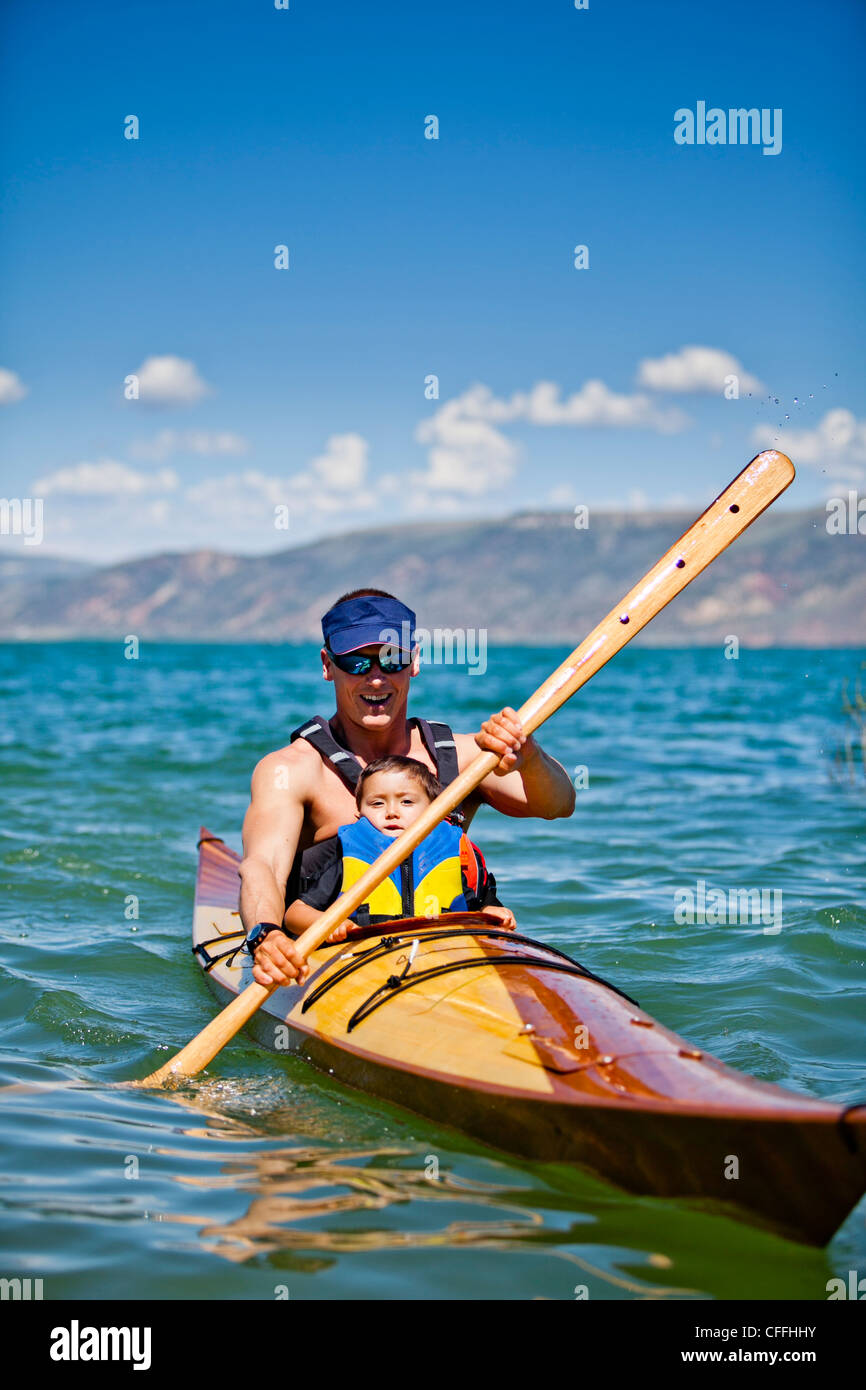 A Man Paddles Wooden Kayak With 3 Year Old Boy Sitting On His Lap Bear Lake