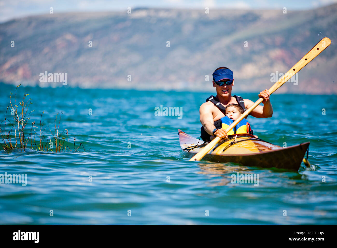 A man paddles a wooden kayak with a 3 year old boy sitting on his lap, Bear Lake. - Stock Image