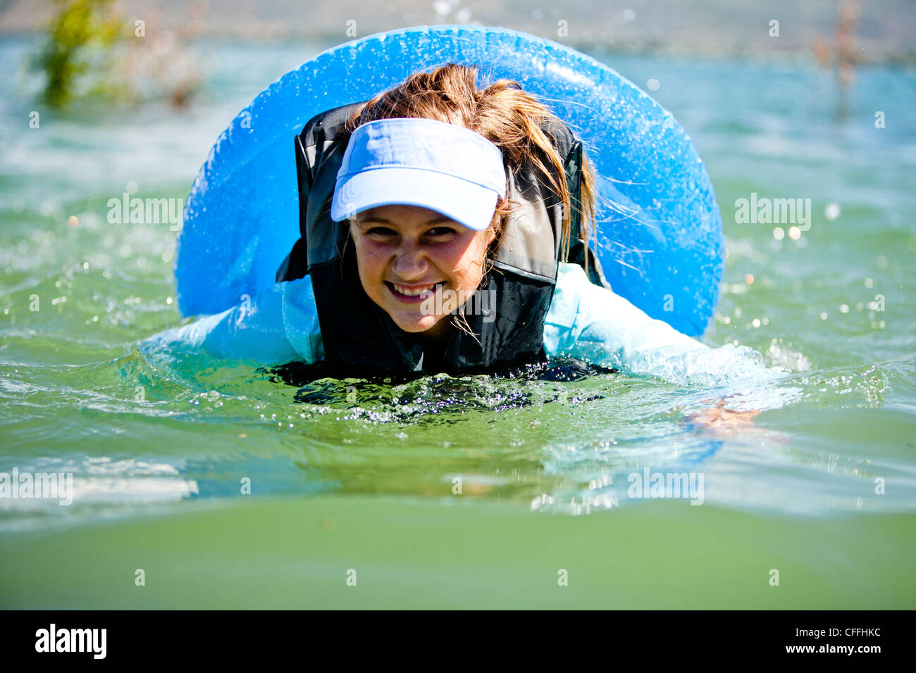 A woman floats and swims on an inner tube, Bear Lake. - Stock Image