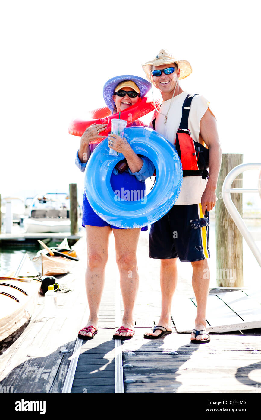 A woman stands with inner tubes and her son next to wooden kayaks at the Bear Lake Marina. - Stock Image