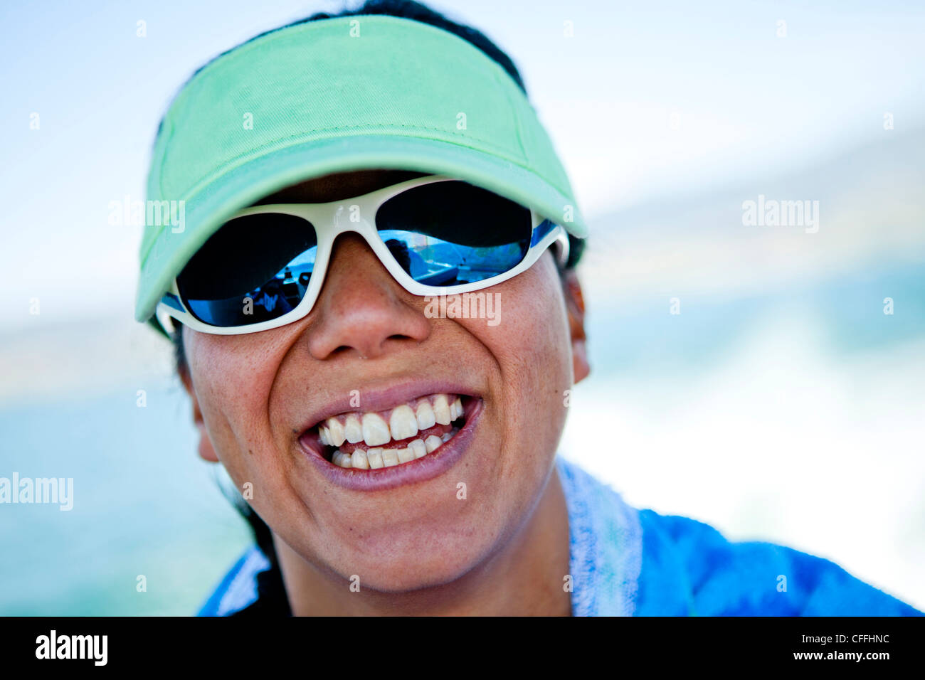 A women in her thirties smiles while wearing a seam foam green visor, Bear Lake, Utah. - Stock Image