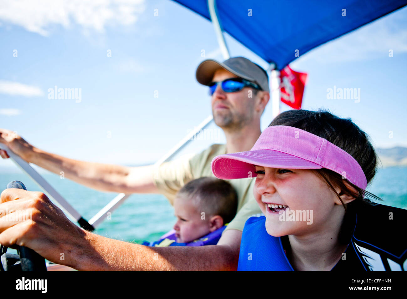 A man pilots a pontoon boat while his three year old son helps steer, and his five year old daughter sits next to - Stock Image
