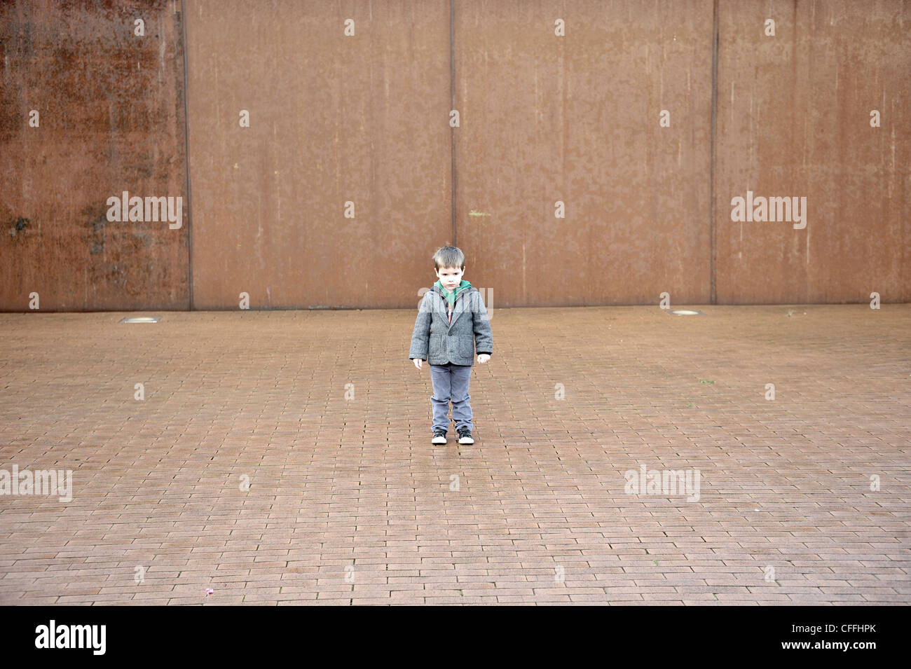 three year old boy portrait rusty background alone - Stock Image