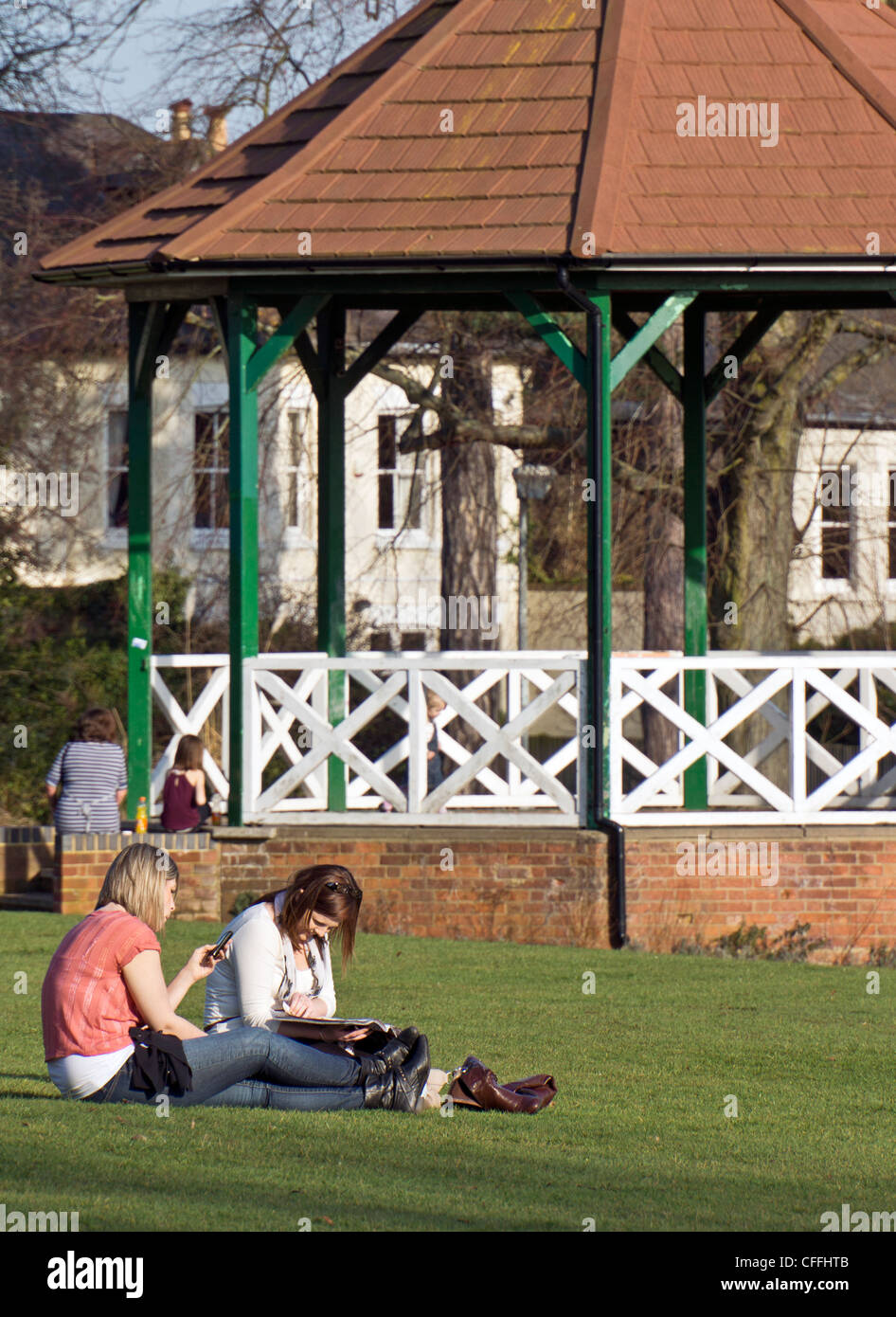 Two women relax on the grass in front of the Bandstand in Leighton Buzzard - Stock Image