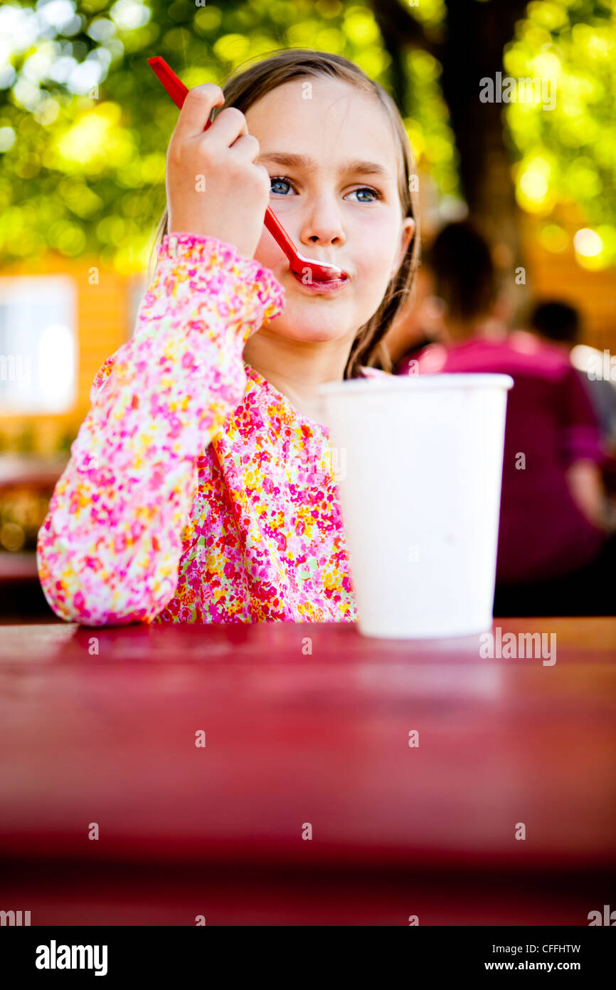 An eight year old girl, eats ice cream while sitting at red picnic table, Garden City, Utah. - Stock Image