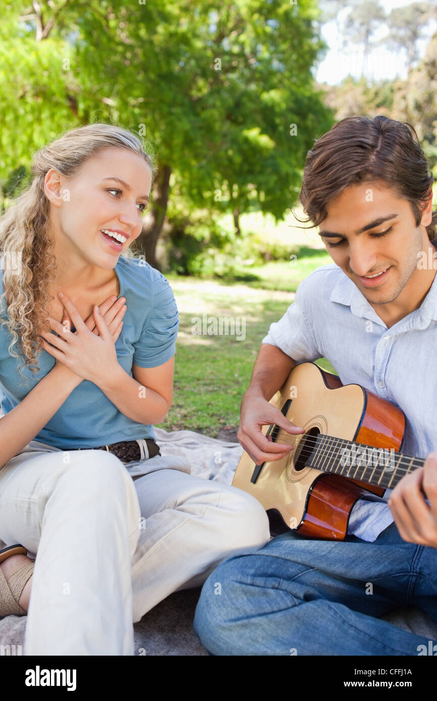 Man impressing his girlfriend by playing a guitar - Stock Image