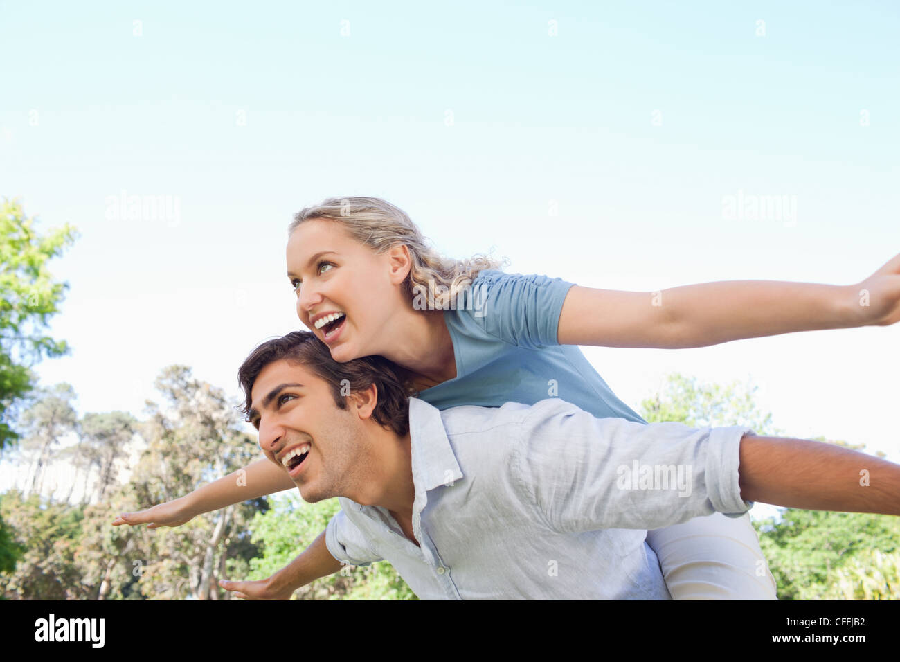 Man carrying his his friend on his back while she spreads her arms - Stock Image
