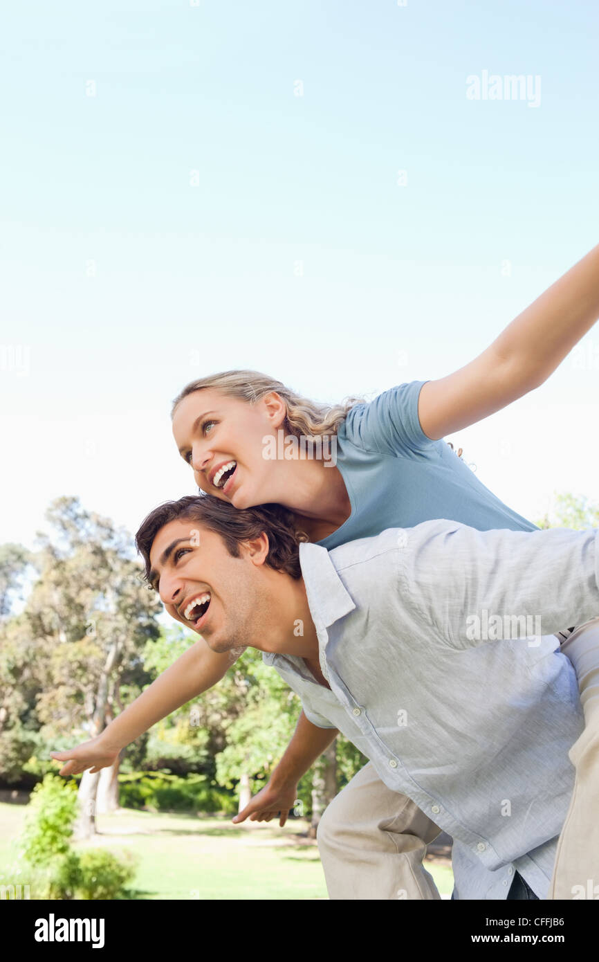Smiling man carrying his his friend on his back while she spreads her arms - Stock Image