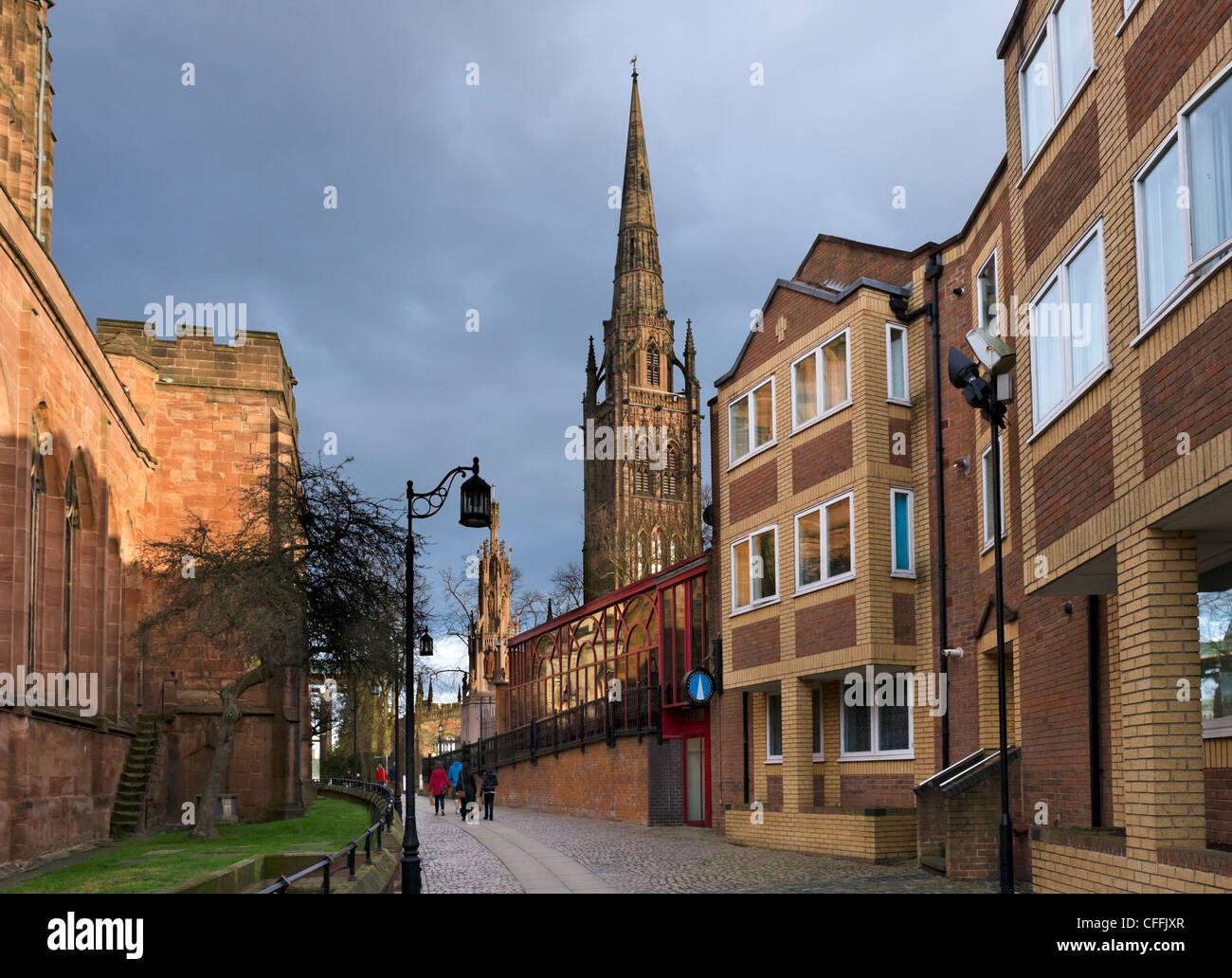 The spire of the old cathedral in the late afternoon with Holy Trinity Church to the left, Coventry, West Midlands, - Stock Image