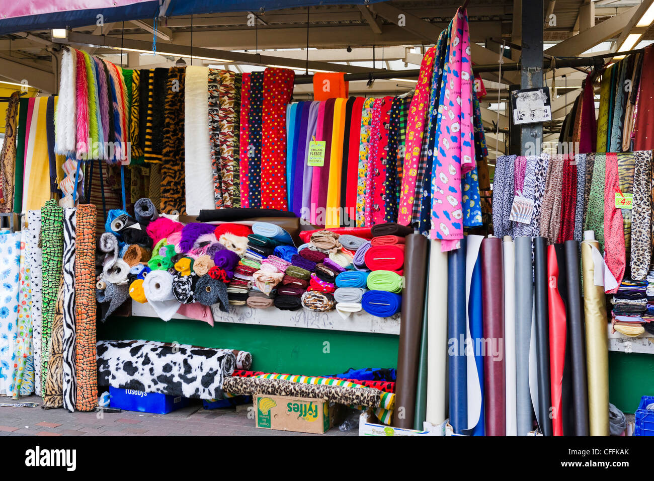 Colourful cloth for sale at the market in the city centre, Leicester, Leicestershire, England, UK - Stock Image
