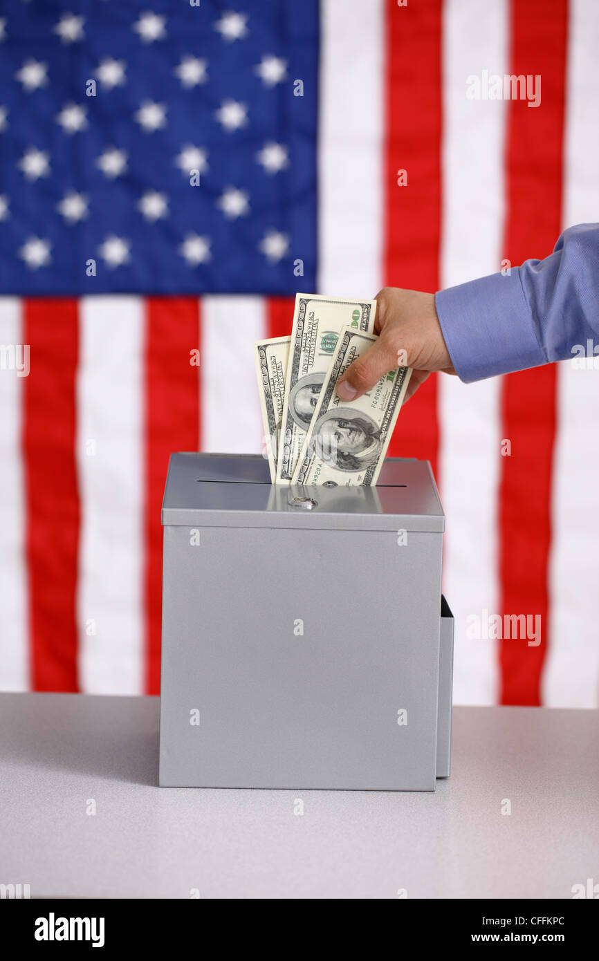 Hand putting money into ballot box, voting and bribery concept, American flag background - Stock Image