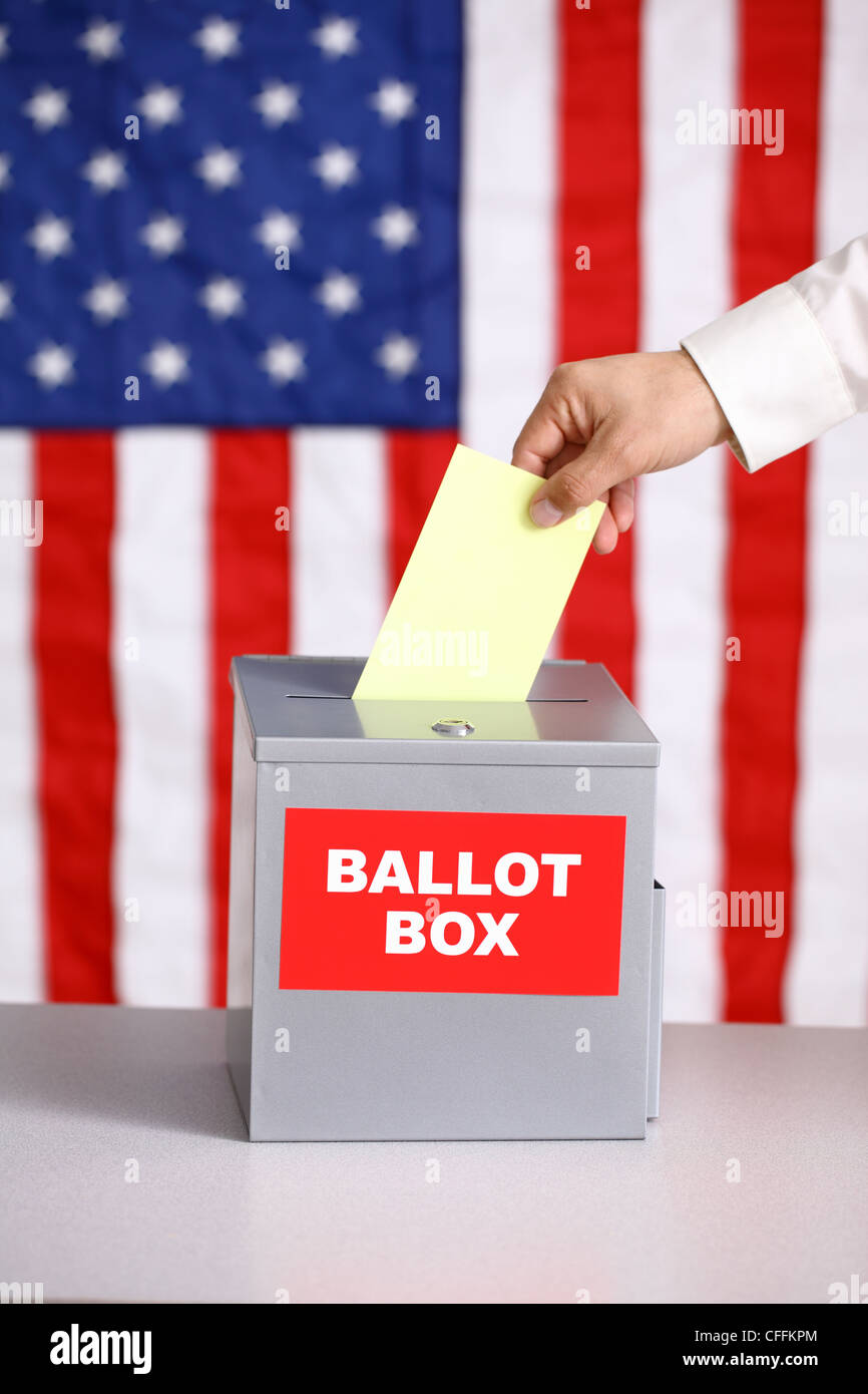 Hand putting ballot into ballot box, voting concept, American flag background - Stock Image