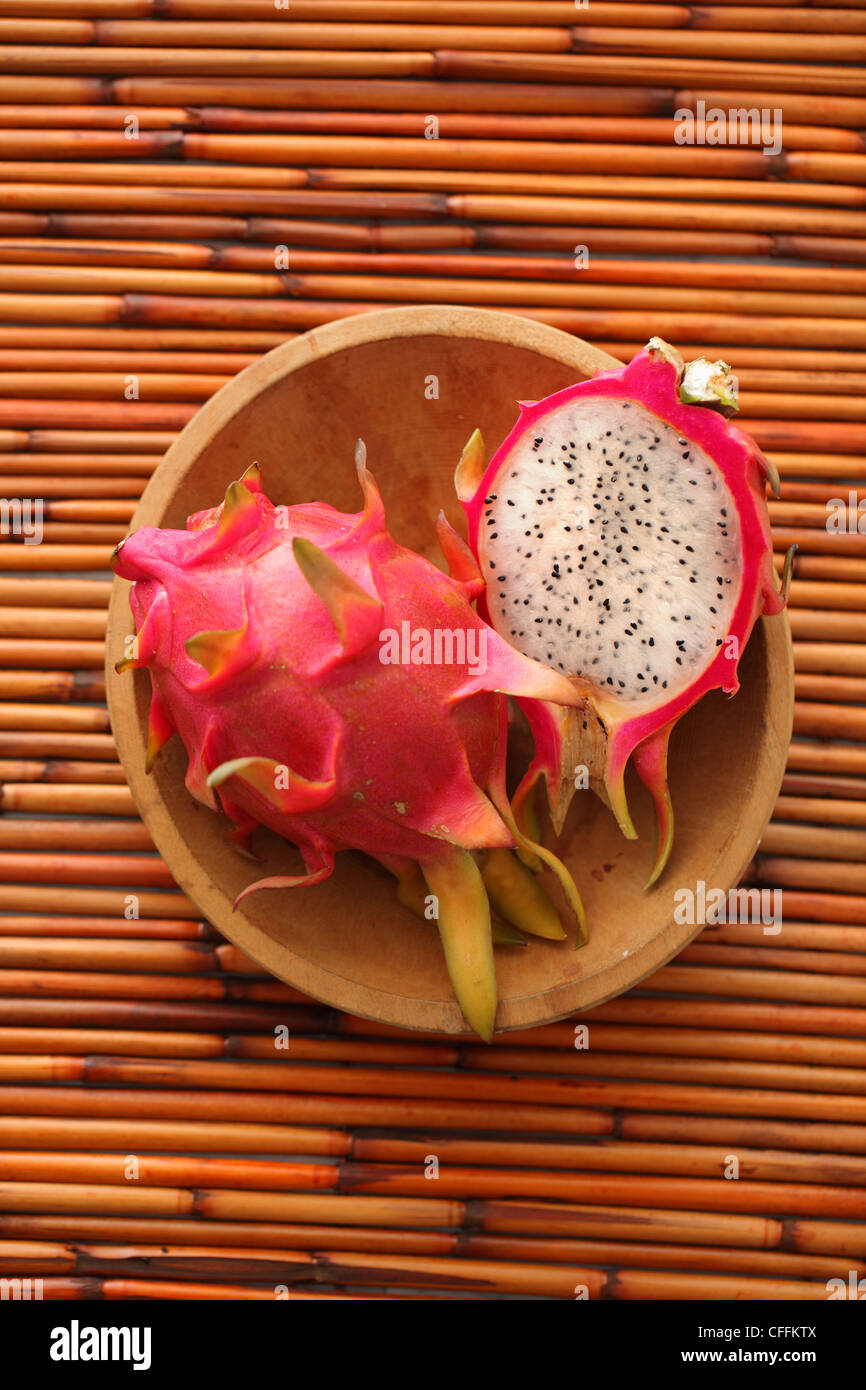 Whole and half dragon fruit in wooden bowl on bamboo background - Stock Image