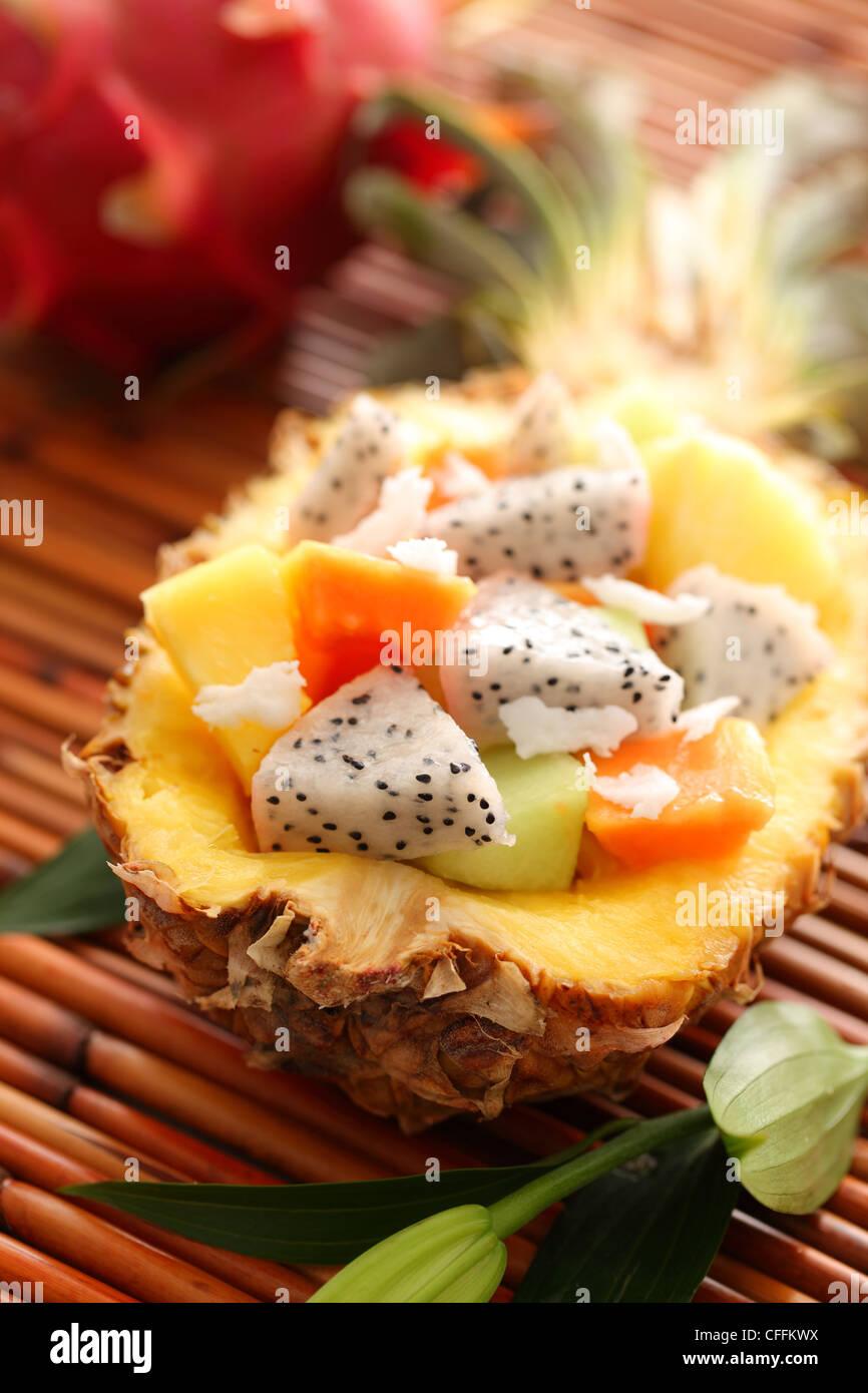 Tropical salad with dragon fruit and papaya inside pineapple - Stock Image