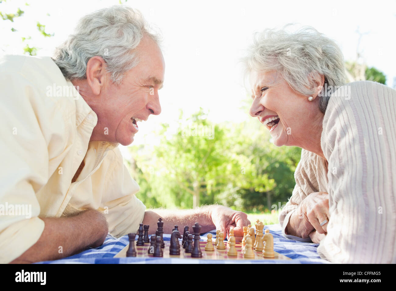 Two friends laughing while playing chess Stock Photo
