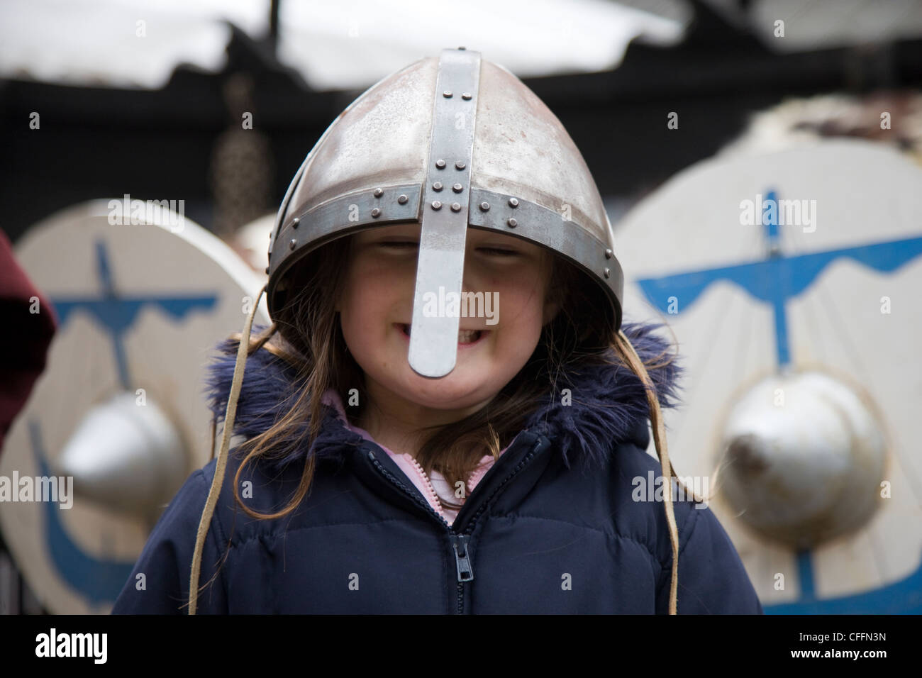 Girl dressed up as a viking warrior with sword, helmet and shield outside the Jorvik Centre in York - Stock Image