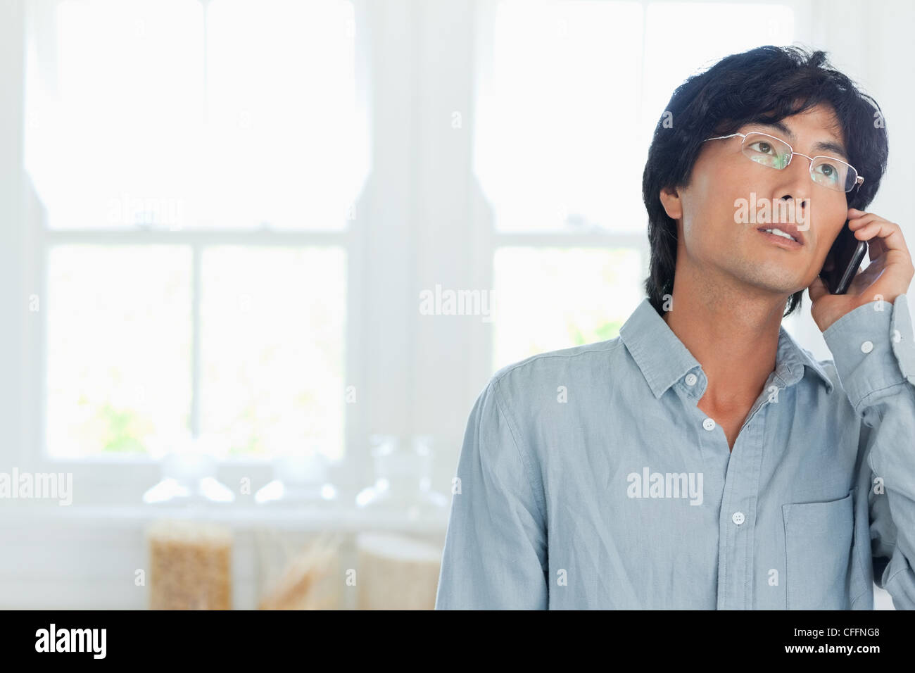 A man looks upwards as he talks on the phone - Stock Image