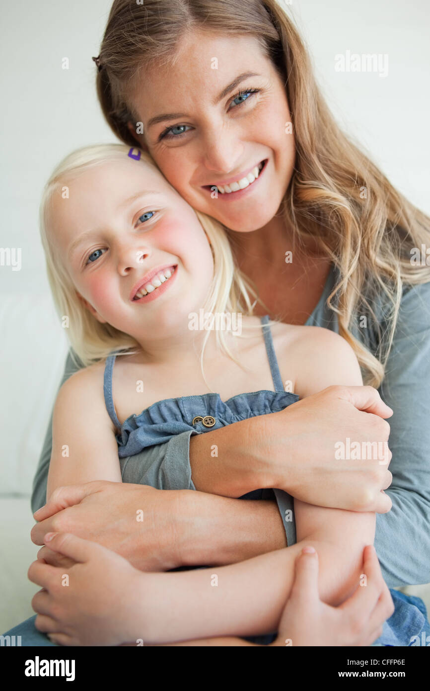 Close up of a smiling mother and daughter as they look ahead with their heads tilted - Stock Image