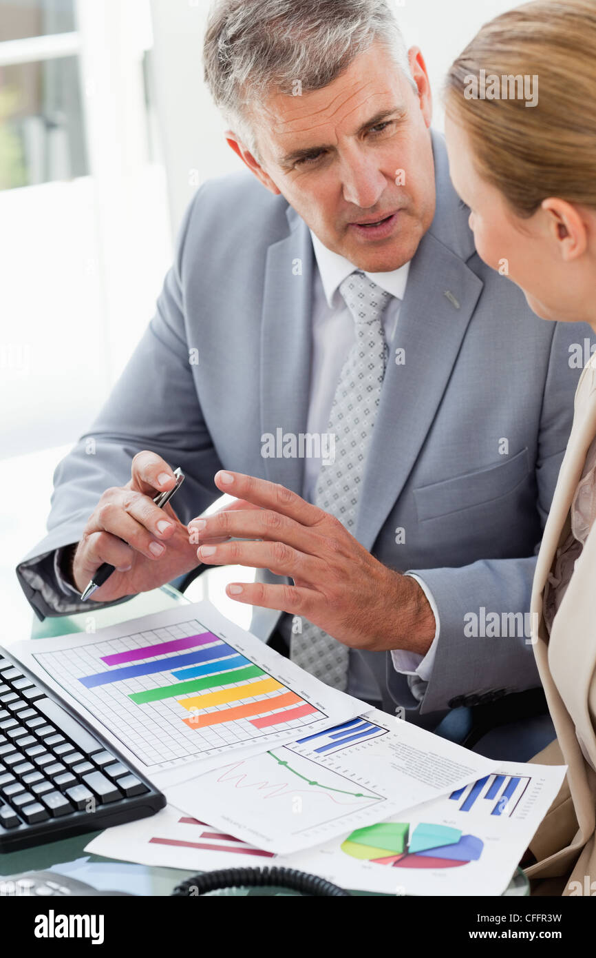 Business people working on statistical review - Stock Image