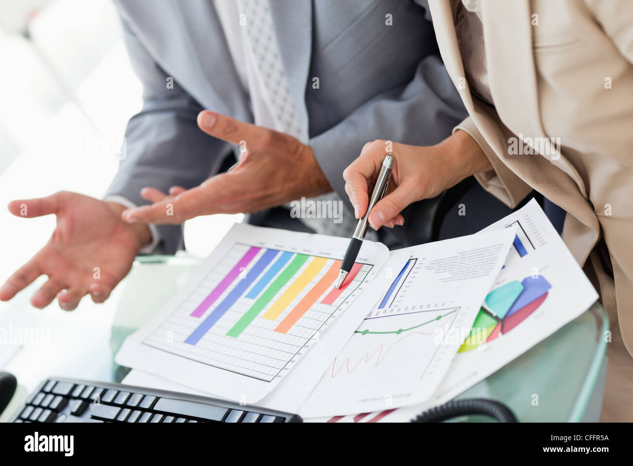 Business people working on statistics - Stock Image