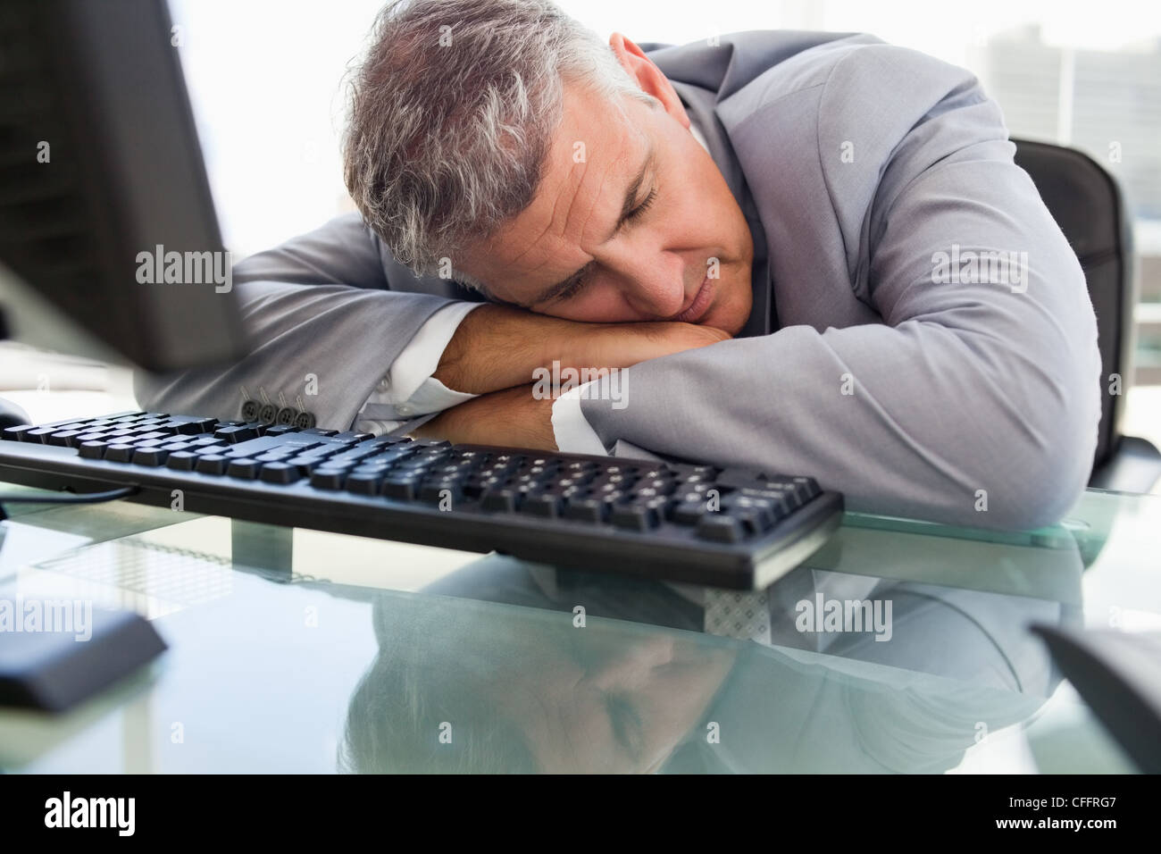 Businessperson sleeping on his desk - Stock Image