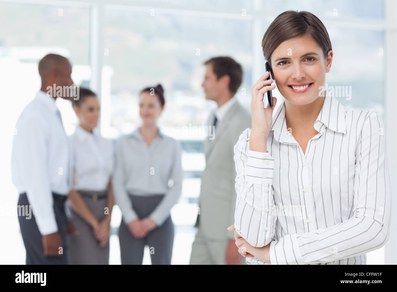 Smiling saleswoman on her mobile phone with associates behind her - Stock Image