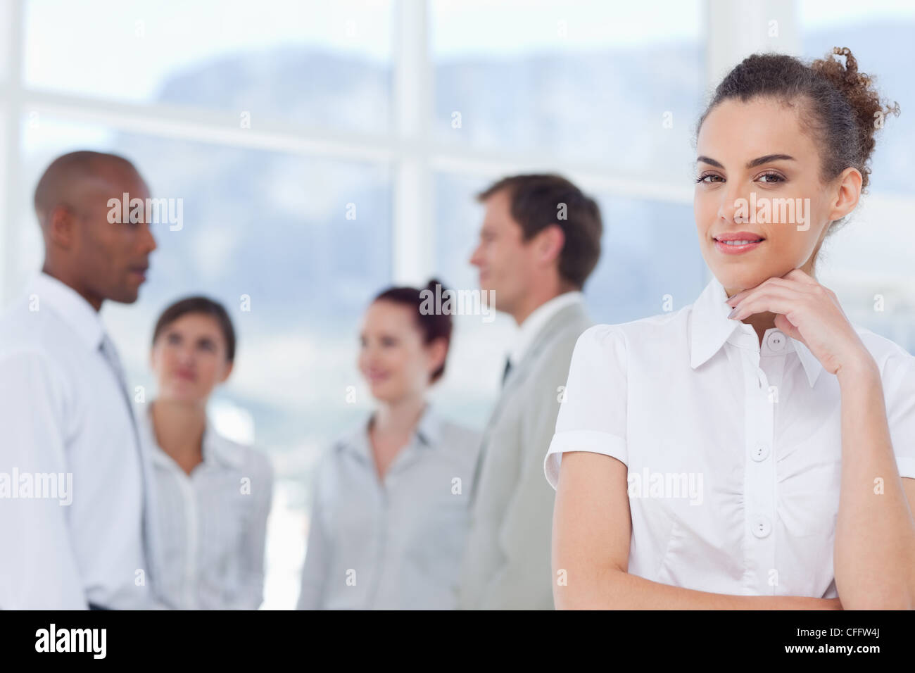 Tradeswoman in thinkers pose with colleagues behind her - Stock Image