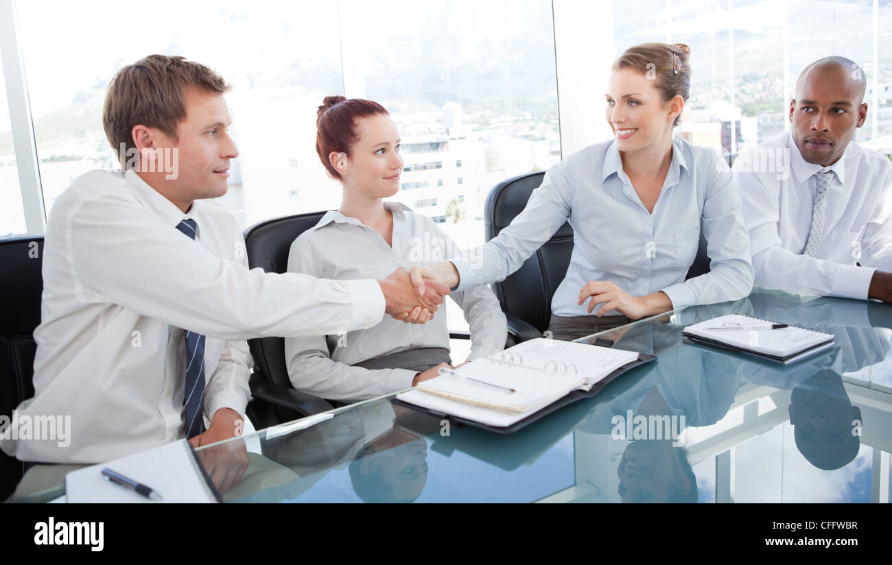 Business team welcoming the newest member to the group - Stock Image