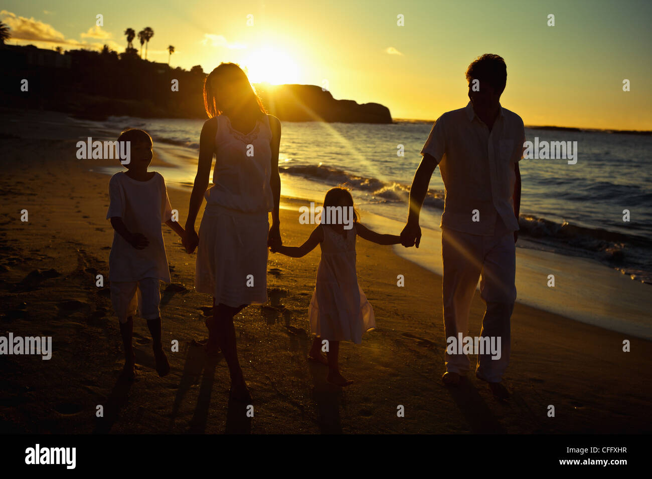 Family walking on the beach while the sun shines on their back - Stock Image