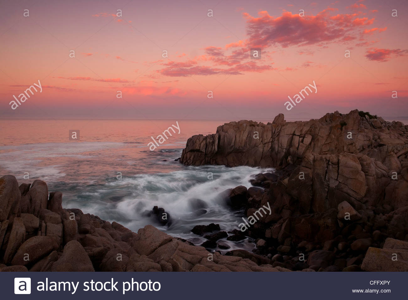 Pacific Ocean waves crash into a narrow, rocky inlet at Lovers Point in Pacific Grove, California. - Stock Image