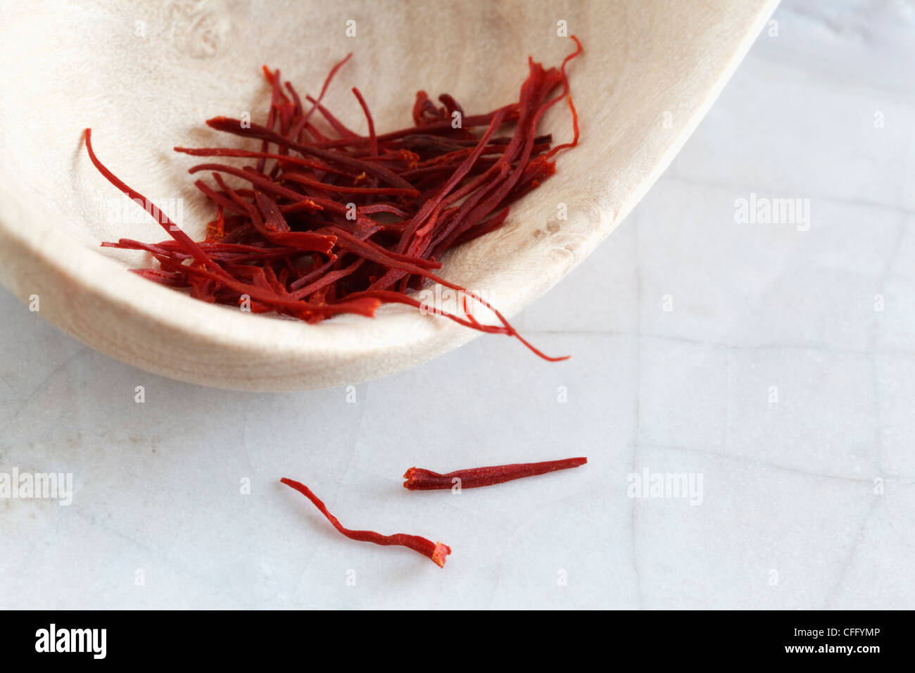 Saffron threads on a wooden spoon with copy space. - Stock Image