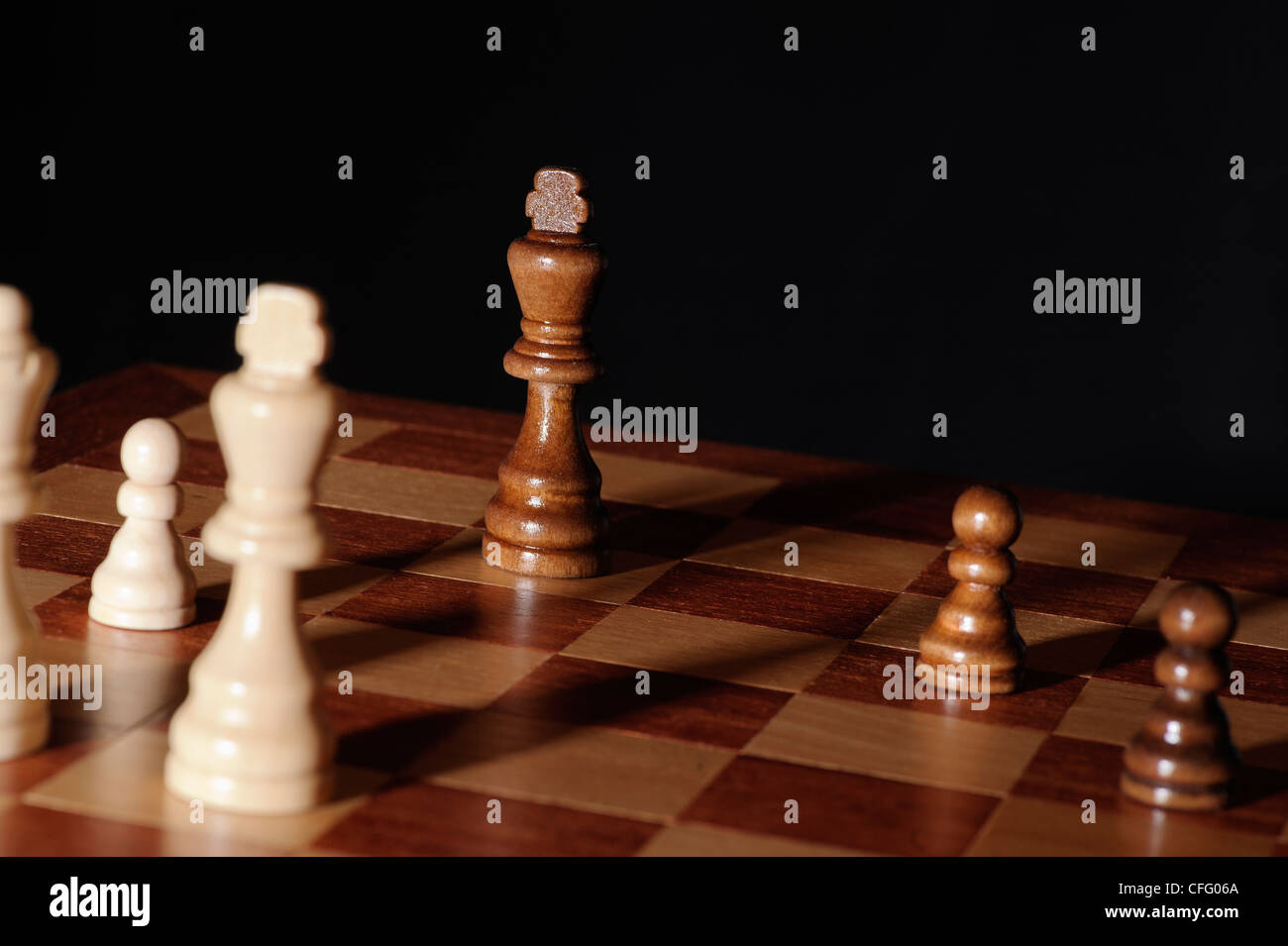 Chess endgame - king under pressure. Dramatic scene with long shadows and black background. - Stock Image