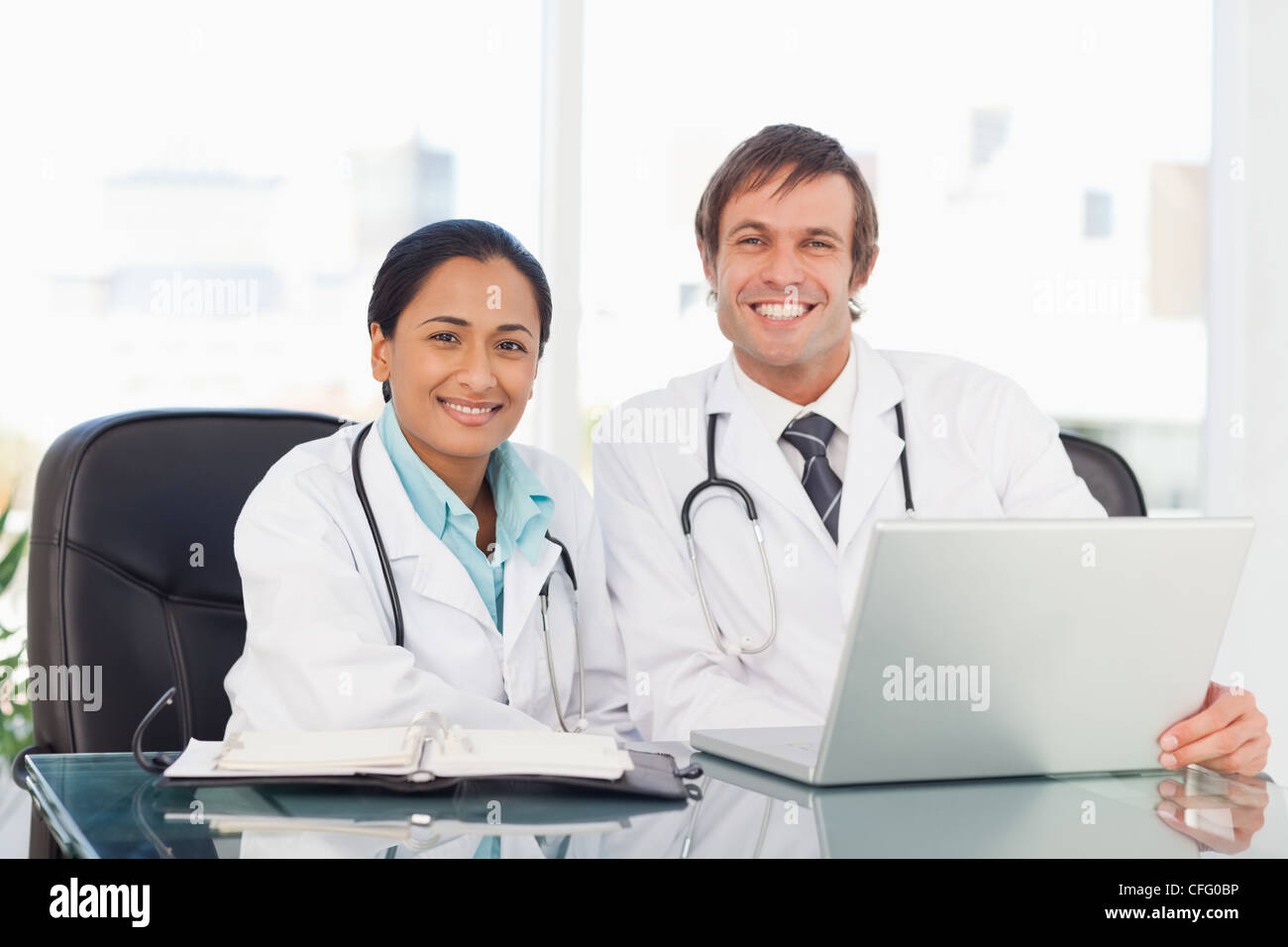 Smiling doctor sitting in front of his laptop while being accompanied by a colleague - Stock Image