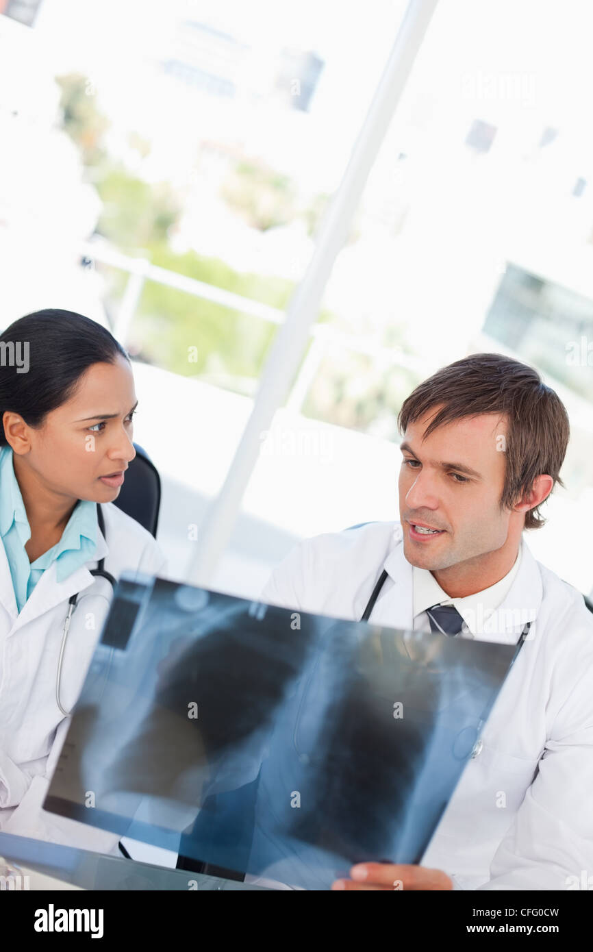 Serious doctor holding an x-ray while being accompanied by a colleague - Stock Image