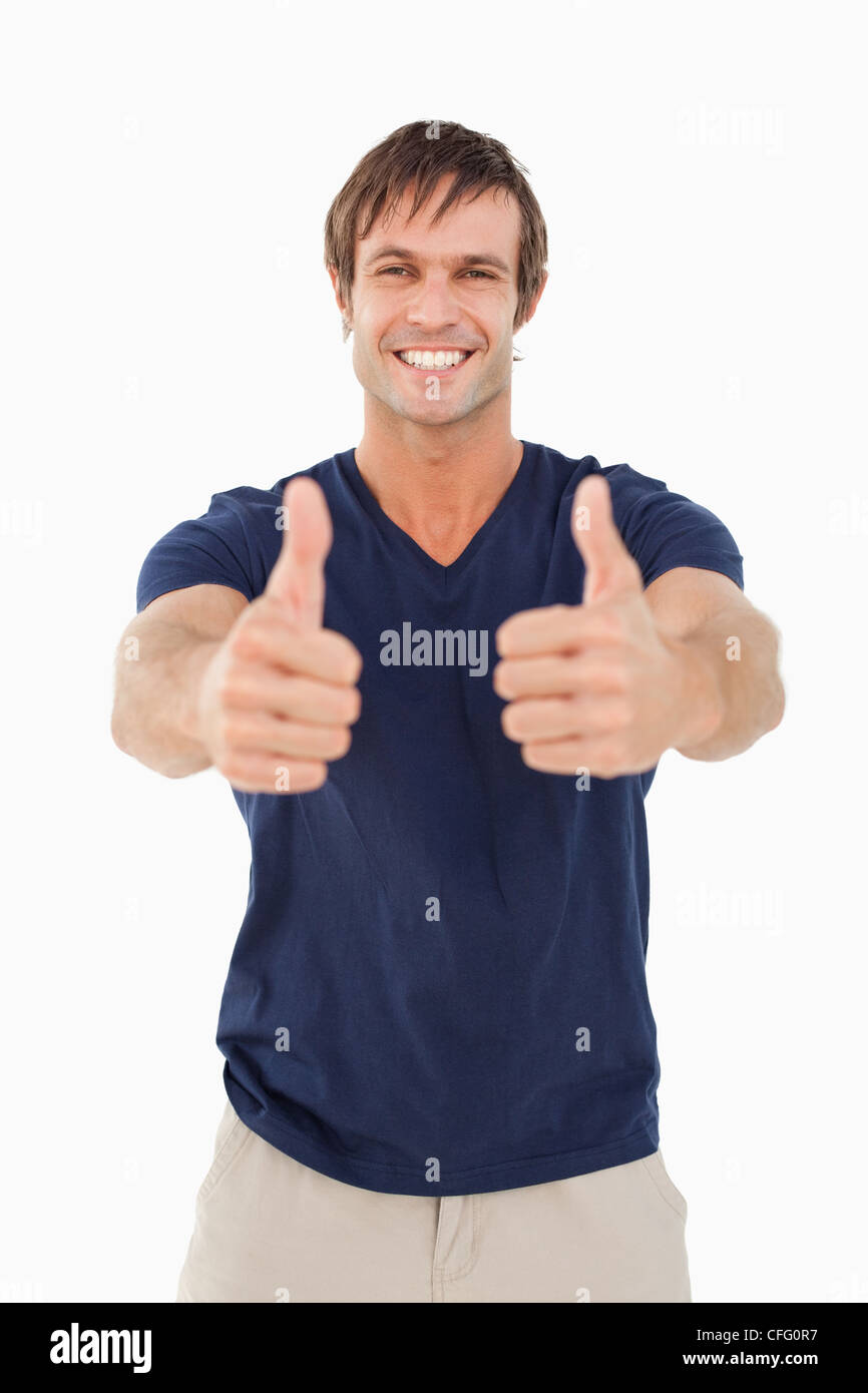 Smiling man with his thumbs up in satisfaction while standing up - Stock Image