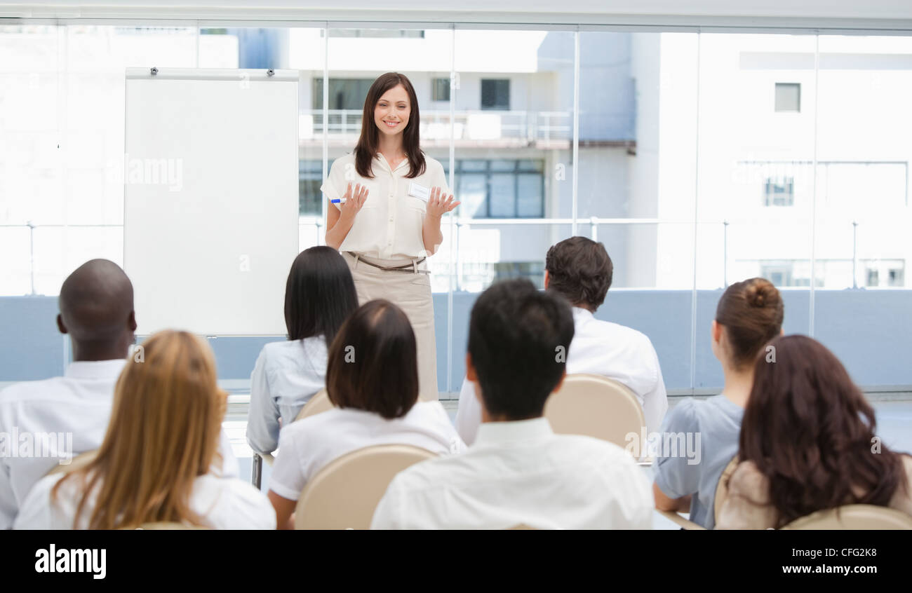 Businesswoman gesturing towards an audience during a presentation - Stock Image
