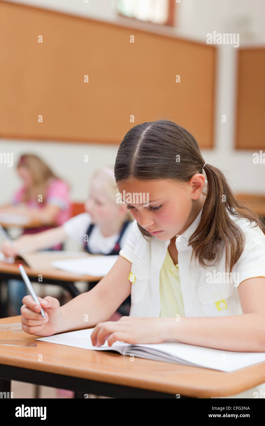 Primary student working on exercise book - Stock Image