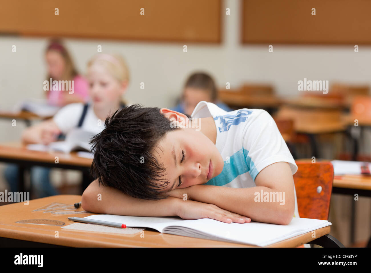 Schoolboy sleeping at desk - Stock Image