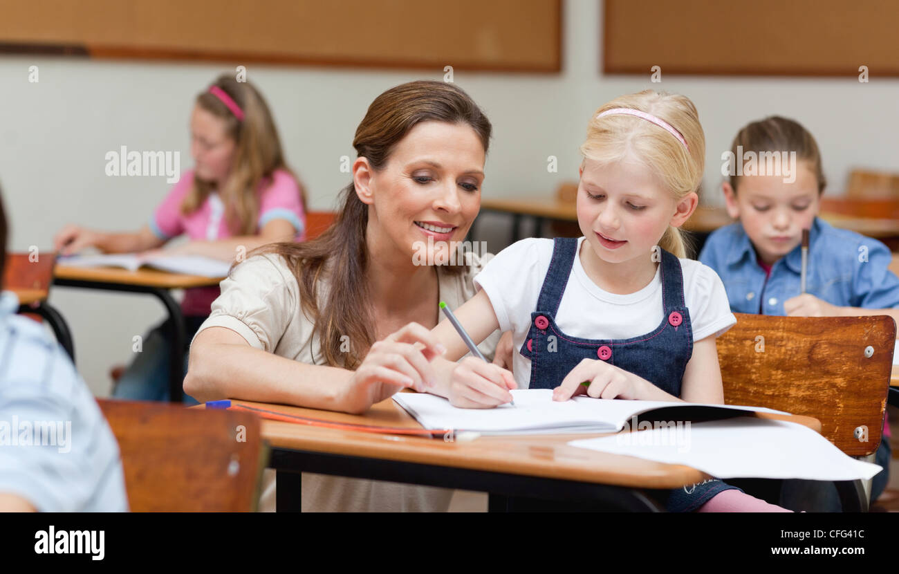 Primary school teacher helping student - Stock Image