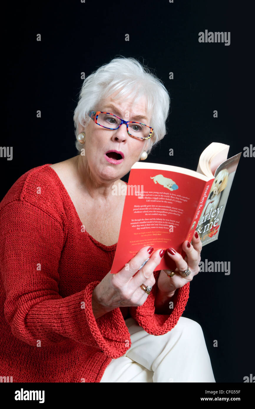 Attractive senior lady in bright clothes with a surprised look on face sitting reading book taken against a black Stock Photo