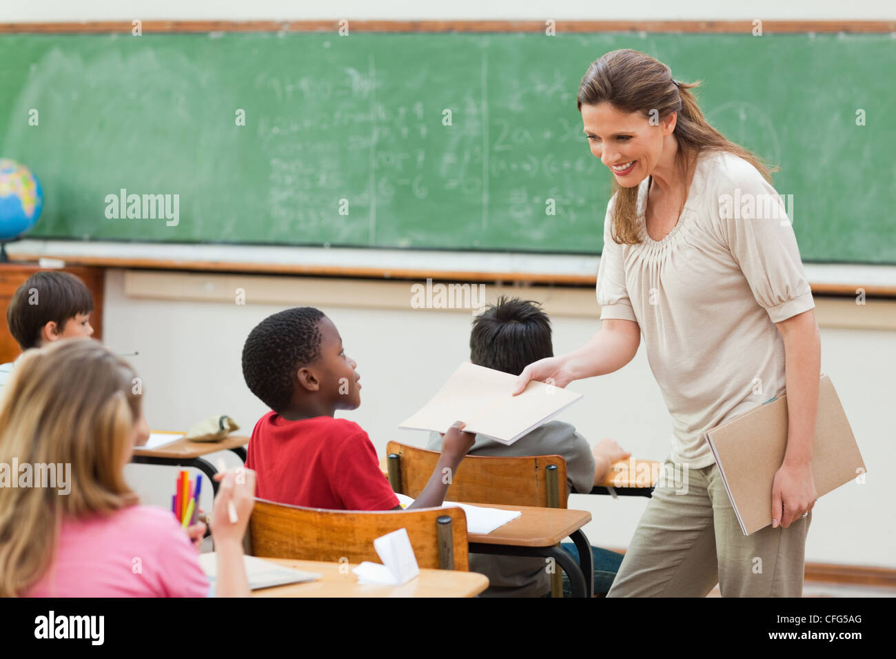 Teacher collecting her students exercise books - Stock Image