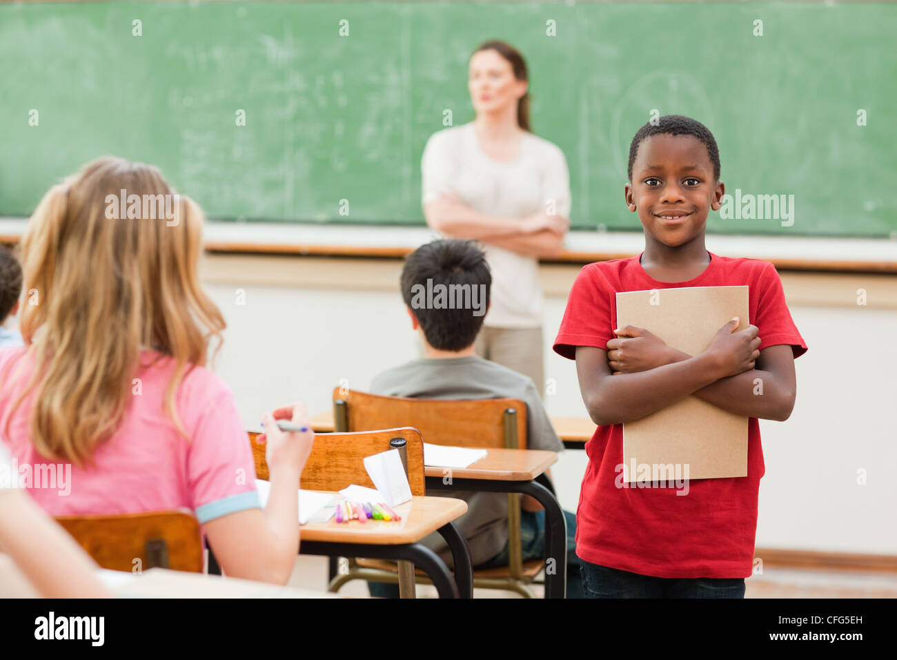 Student standing in class with his exercise book - Stock Image