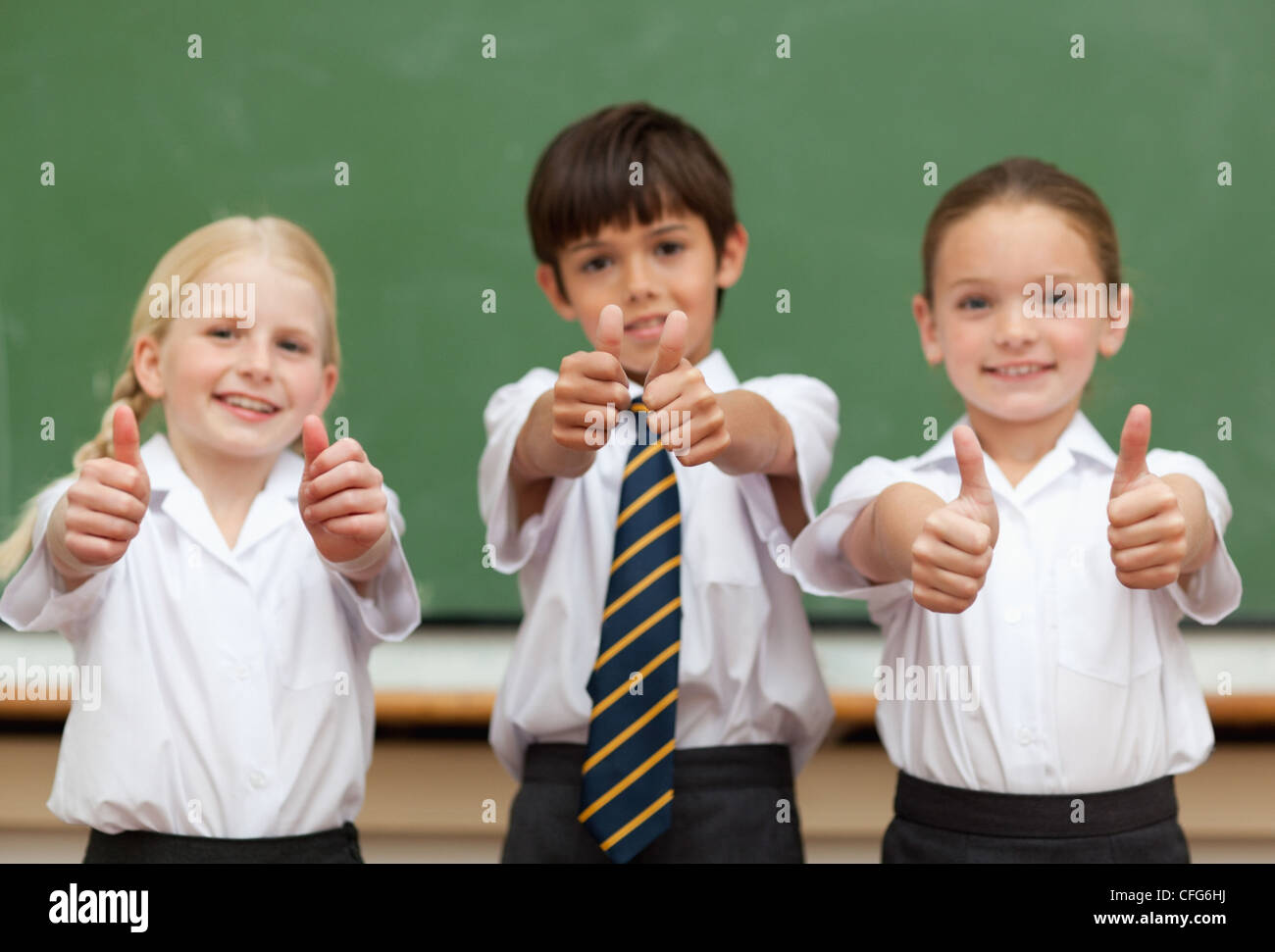 Smiling schoolchildren giving thumbs up - Stock Image