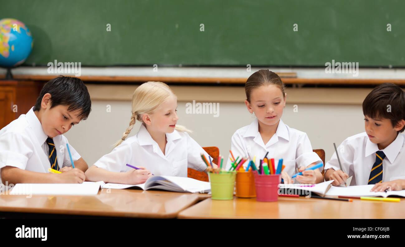 Schoolchildren in school uniforms painting at desk - Stock Image