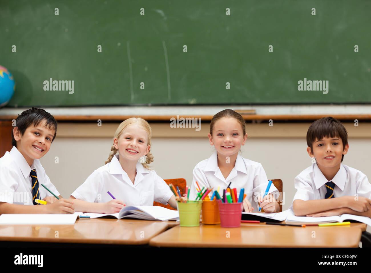 Smiling schoolchildren sitting at desk together - Stock Image