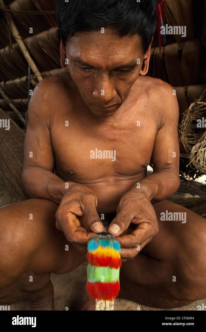 Huaorani Indian, Tage Kaiga, making feather crown. Gabaro Community, Yasuni National Park, Amazon rainforest, Ecuador - Stock Image
