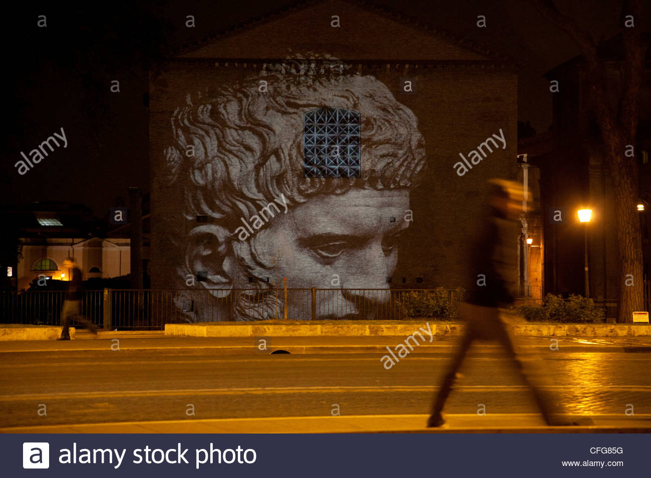 Pedestrians underneath a projection of Julius Caesar on a rainy night. - Stock Image