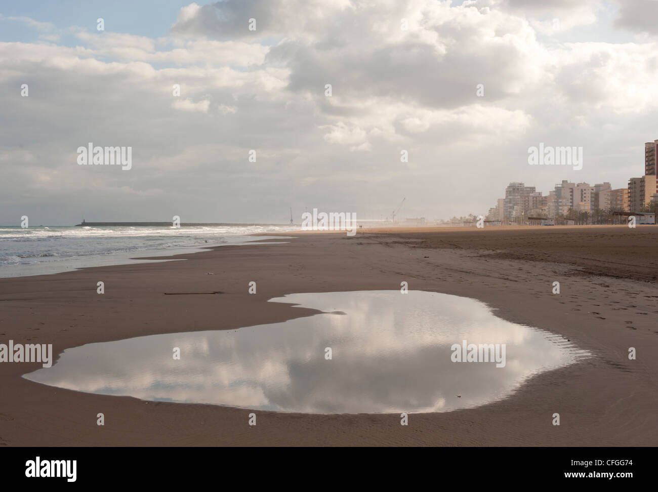 A large puddle reflects a stormy cloudy sky above the sea as rain sets in during winter on the Spanish resort of - Stock Image
