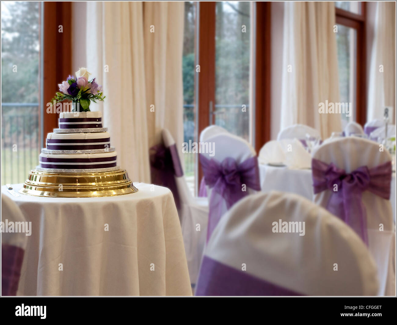 Purple And Gold Wedding.A White Purple And Gold Wedding Cake Sits On A Table In An